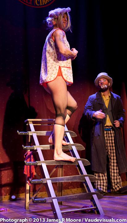 Stephanie Monseu performs a sideshow stunt climbing a machete ladder.
