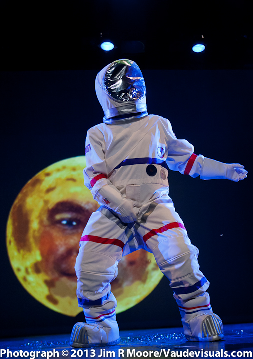 David Leslie dances in a space suit as Tom looks on from the moon.